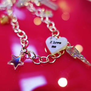 Close up of I love me charm necklace choker with star and lightning bolt charms  on red background