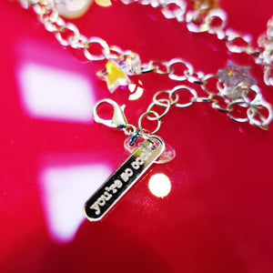 Close up of You're so cool on I love me charm necklace choker with star and lightning bolt charms  on red background