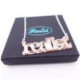 realist literary necklace in rose gold mirror close up on box