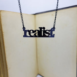 realist literary necklace hanging in front of book