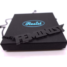 Load image into Gallery viewer, slate frost all caps feminist necklace on box