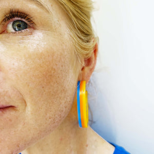Model wears Roller Disco sunflower yellow orange and blue Suffragette trio in Parma violet, white and avocado Mary Beard Women & Power earrings, statement hoops