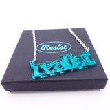 close up of realist literary necklace in teal mirror