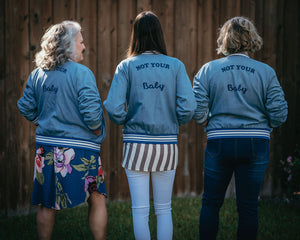 "Kathy, Jessica, and Meggie stand with their backs to the camera sporting the Motley Denim Bomber with ""Not Your Baby"" embroidered on the back."