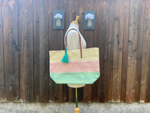 A tote is resting on the shoulder of a mannequin. The tote bag is in colorblock with gold, pink, and green. It also has a teal green tassel and brown leather handles.