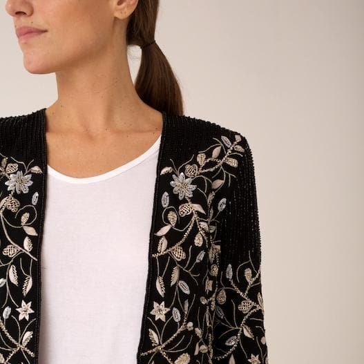 A beautiful cropped bolero jacket with sharp cuts and delicate floral embroidery