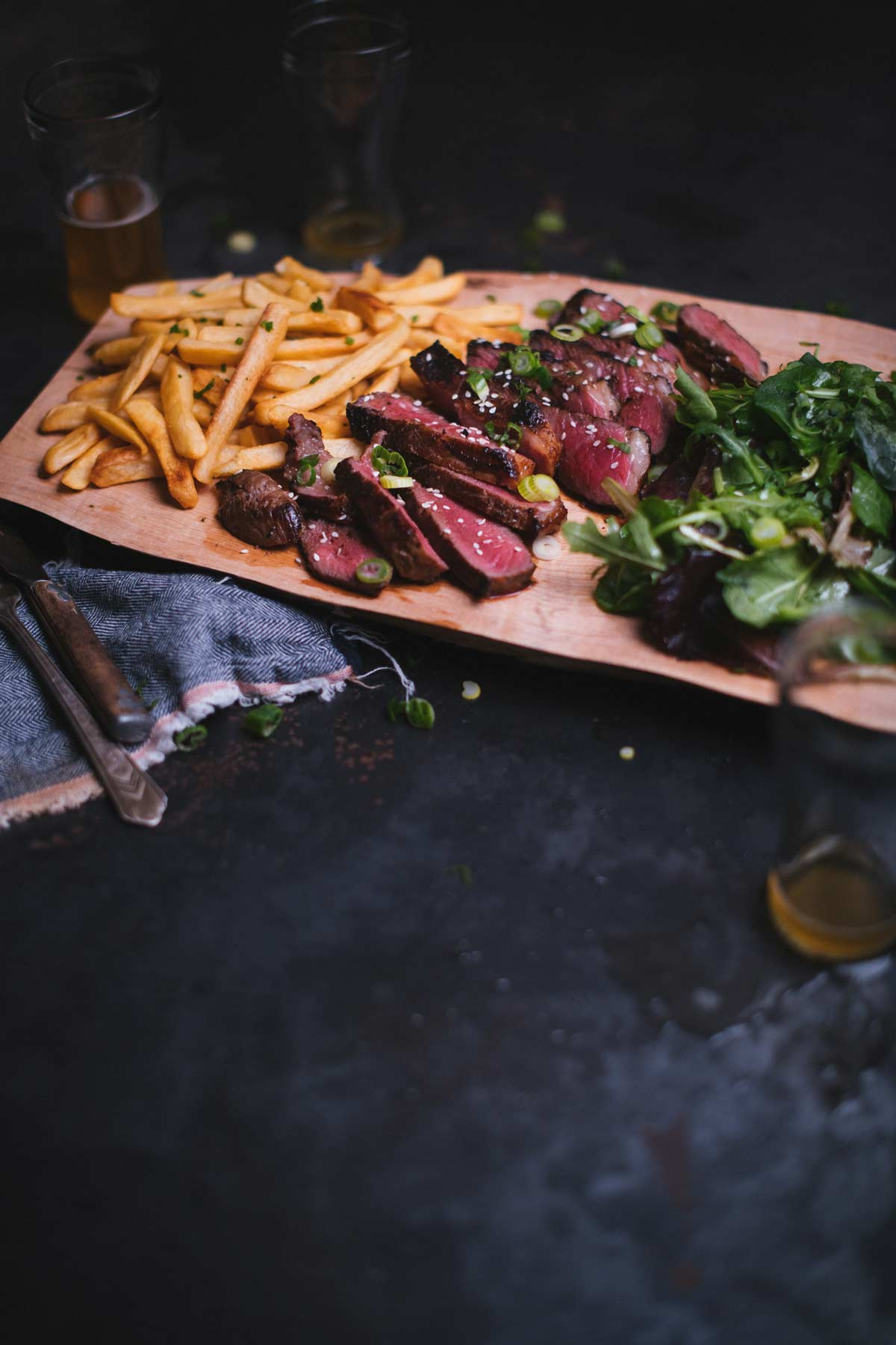 sliced medium rare steak, french fries, green salad