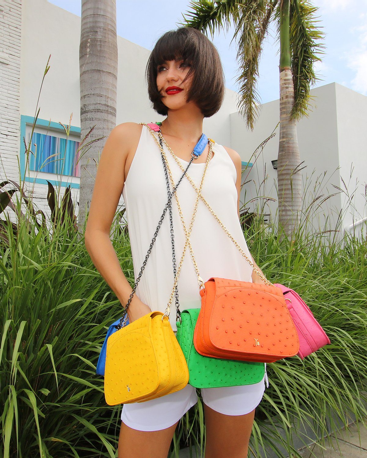Ostrich Bags Pretty Happy Model with Benny Crossbody Handbags in Colors Sustainable Genuine Ostrich in Miami Deco Background and Palms