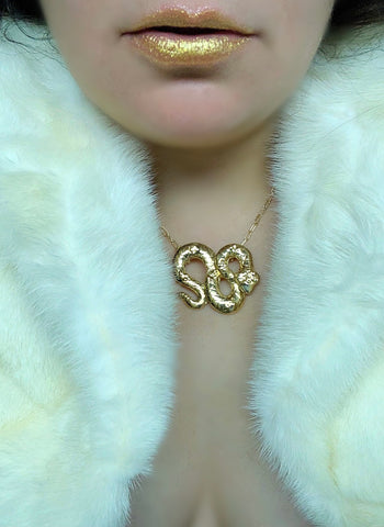 Brunette female wearing a white fur coat and the grand serpent necklace in yellow gold plated brass