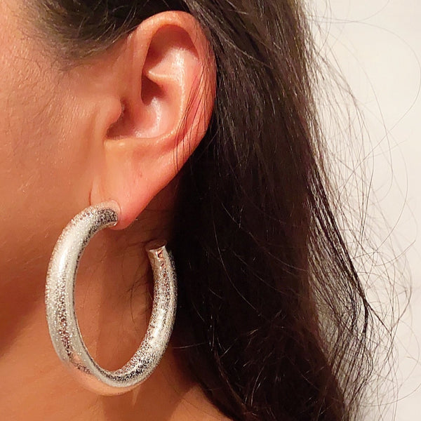 Sterling silver filled textured hoops worn by a female with dark brown hair color