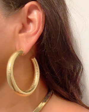Yellow Gold filled hoop earrings textured worn by a female with darm brown hair color