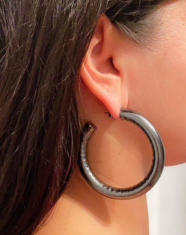 Gunmetal color hoops earring worn by a female with brunette hair color