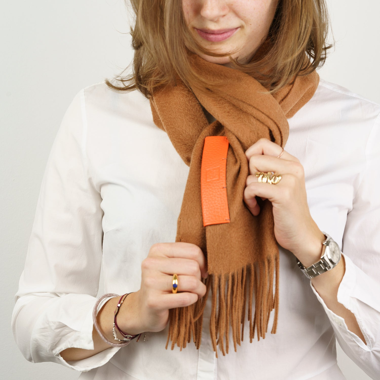 The Biellese Cashmere scarf with Calfskin leather. 100% Cashmere & R. Horn´s Calfskin Leather 30 x 180 cm. Made in collaboration with R. Horn Vienna. Pictured: Beige Cashmere with Orange leather label