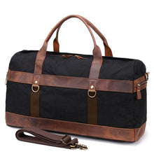 Load image into Gallery viewer, This black vintage wax canvas weekend duffel bag is ideal for shorter holidays.   On the inside there's loads of room to keep clothes and a laptop with plenty of space to spare for other items . There are also two smaller pockets at each end for smaller items.  The bottom is protected with five brass studs and it comes with a detachable shoulder strap for convenience.