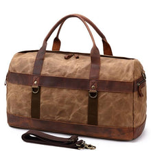 Load image into Gallery viewer, This brown vintage wax canvas weekend duffel bag is ideal for shorter holidays.   On the inside there's loads of room to keep clothes and a laptop with plenty of space to spare for other items . There are also two smaller pockets at each end for smaller items.  The bottom is protected with five brass studs and it comes with a detachable shoulder strap for convenience.
