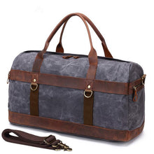 Load image into Gallery viewer, This dark grey vintage wax canvas weekend duffel bag is ideal for shorter holidays.   On the inside there's loads of room to keep clothes and a laptop with plenty of space to spare for other items . There are also two smaller pockets at each end for smaller items.  The bottom is protected with five brass studs and it comes with a detachable shoulder strap for convenience.