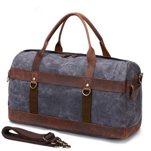 This dark grey vintage wax canvas weekend duffel bag is ideal for shorter holidays.   On the inside there's loads of room to keep clothes and a laptop with plenty of space to spare for other items . There are also two smaller pockets at each end for smaller items.  The bottom is protected with five brass studs and it comes with a detachable shoulder strap for convenience.