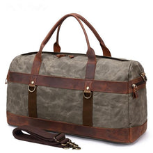 Load image into Gallery viewer, This green vintage wax canvas weekend duffel bag is ideal for shorter holidays.   On the inside there's loads of room to keep clothes and a laptop with plenty of space to spare for other items . There are also two smaller pockets at each end for smaller items.  The bottom is protected with five brass studs and it comes with a detachable shoulder strap for convenience.