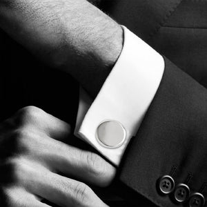 Simple silver coloured round cufflinks pictured in a shirt cuff