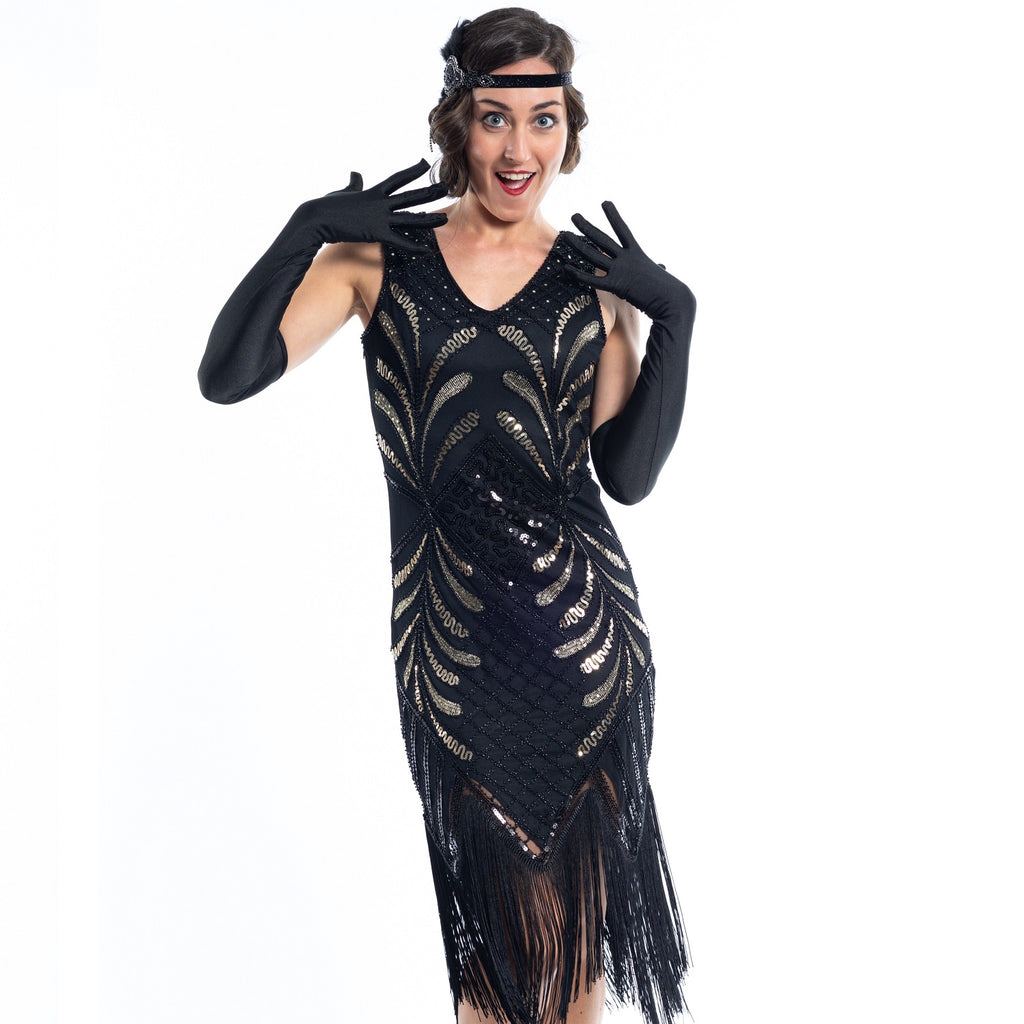 A black vintage flapper dress with black and gold sequins, gold beads and fringes around the hem - close view