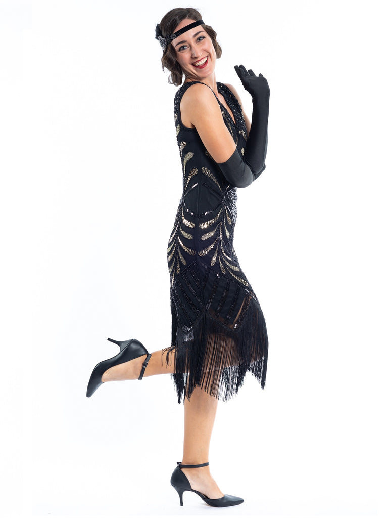 A black vintage flapper dress with black and gold sequins, gold beads and fringes around the hem - side view