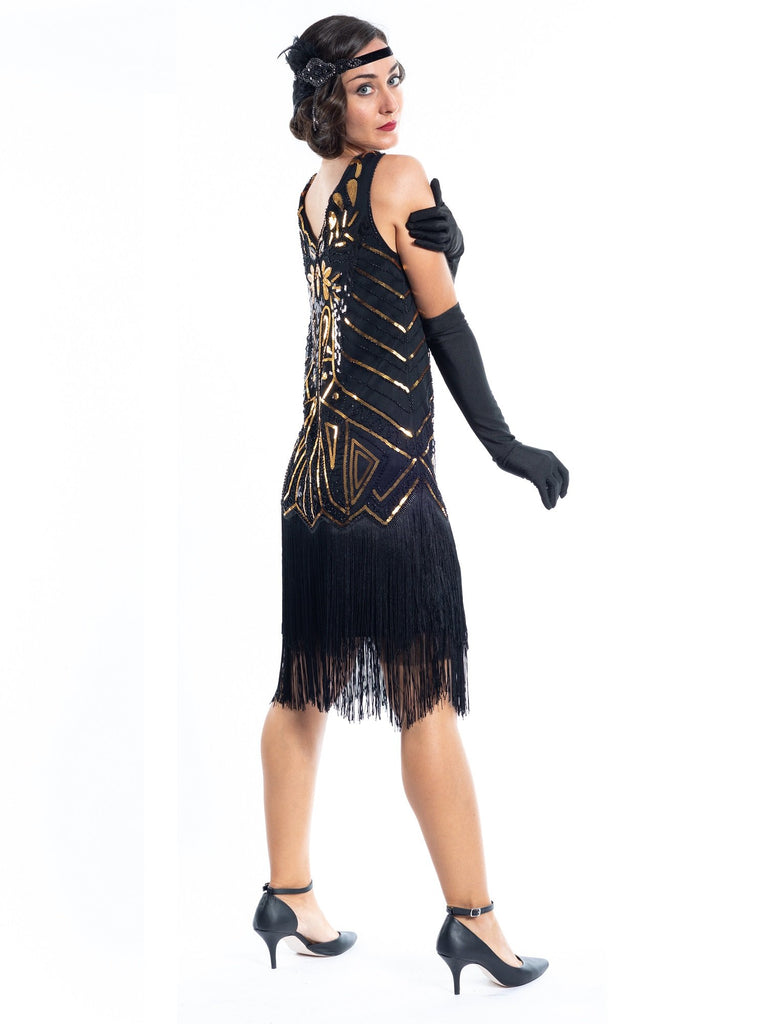 A black flapper dress with gold sequins, beads and black fringes around the hem - Back View