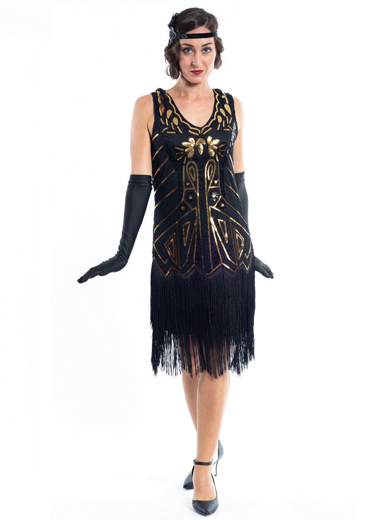 A black flapper dress with gold sequins, beads and black fringes around the hem
