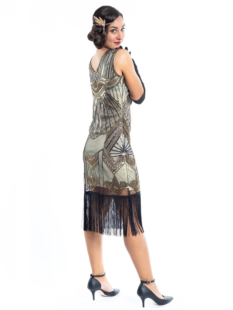 A gold flapper dress with a 1920s deco pattern of sequins, beads and fringes around the hem - back view