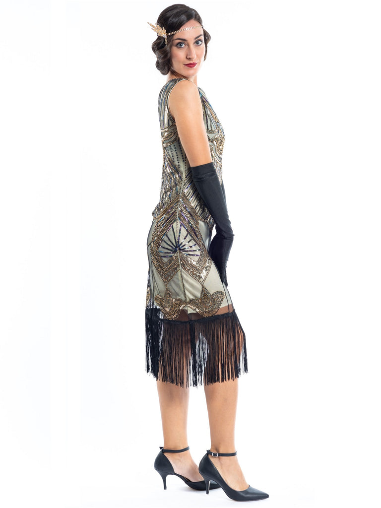 A gold flapper dress with a 1920s deco pattern of sequins, beads and fringes around the hem - side view