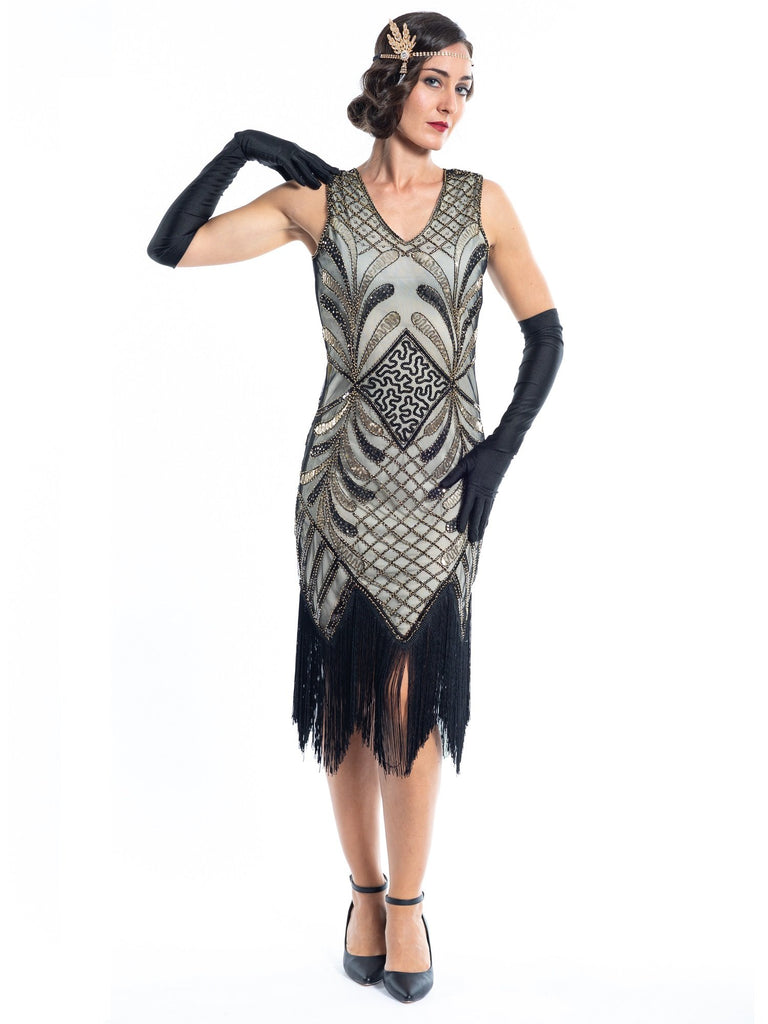 A vintage flapper dress with gold sequins, gold beads and fringes around the hem