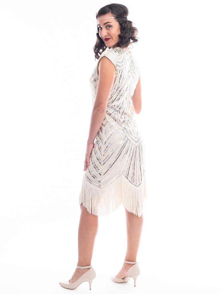 A back view of a vintage 1920s flapper dress in ivory white with beads, sequins and fringes around hem.
