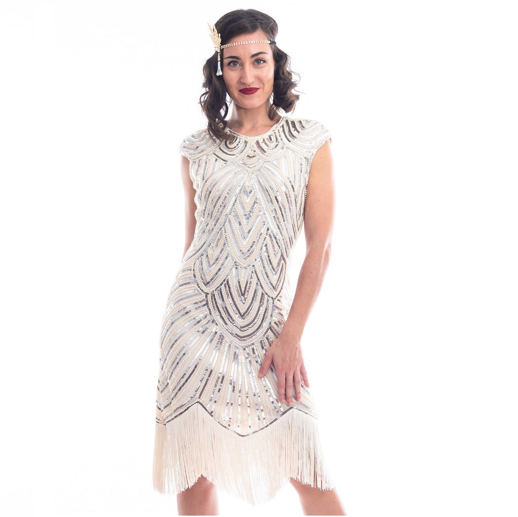 A close view of a vintage 1920s flapper dress in ivory white with beads, sequins and fringes around hem.
