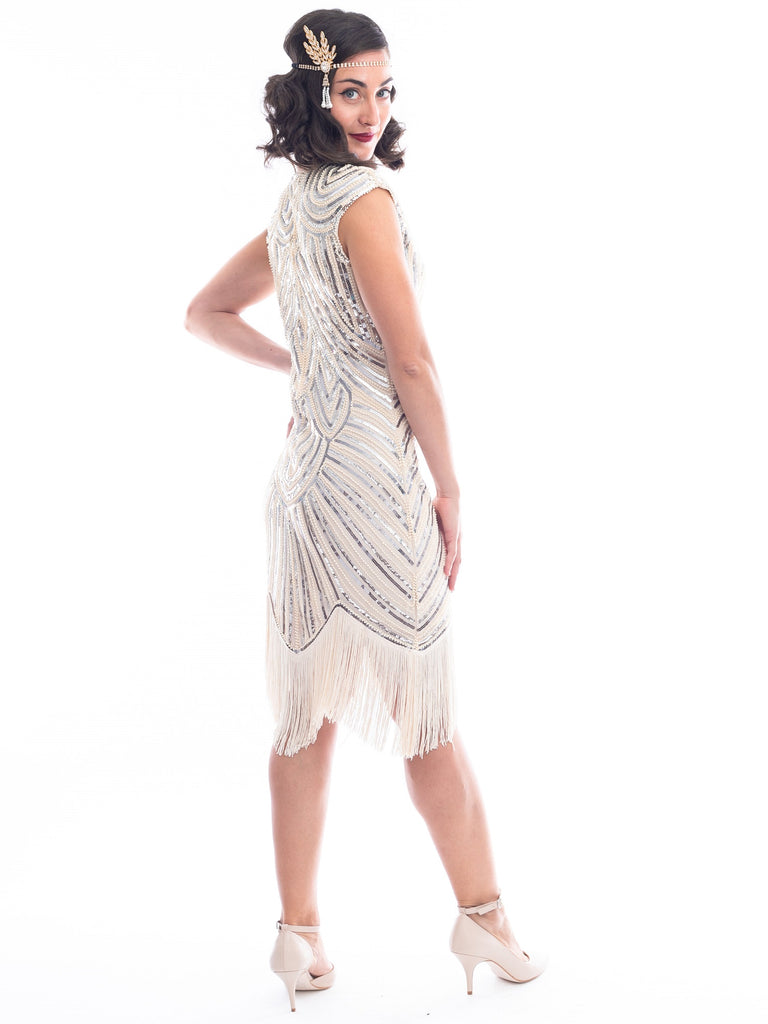 A side view of a vintage 1920s flapper dress in ivory white with beads, sequins and fringes around hem.