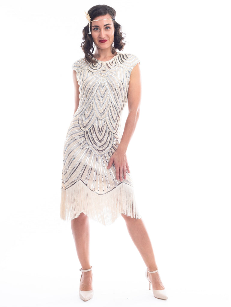 A vintage 1920s flapper dress in ivory white with beads, sequins and fringes around hem.