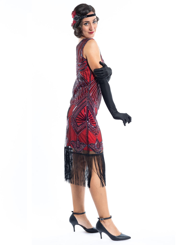 A red flapper dress with a 1920s deco pattern of sequins, beads and fringes around the hem - side view