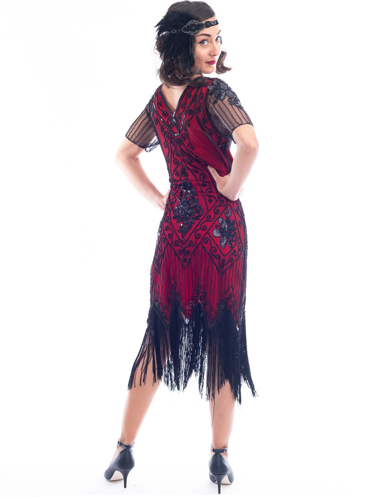 A back view of a burgundy red 1920s Flapper Dress with black beads, sequins, sheer sleeves and black fringes