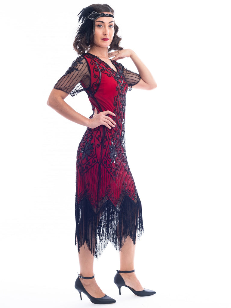A side view of a burgundy red 1920s Flapper Dress with black beads, sequins, sheer sleeves and black fringes
