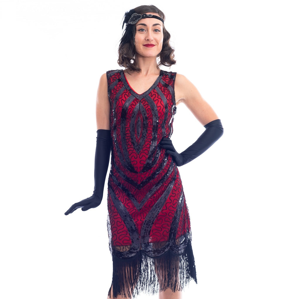 A close up view of a Red Gatsby Dress with a deco pattern of black sequins, scrawls of black beads and fringe around the hem