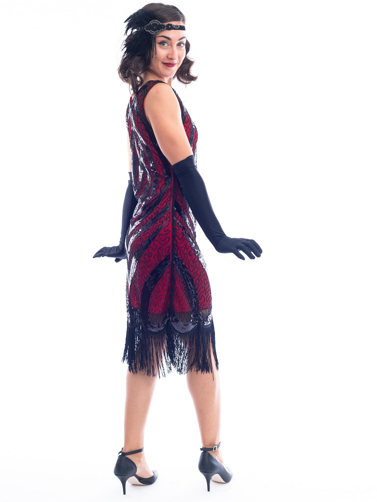 A side view of a Red Gatsby Dress with a deco pattern of black sequins, scrawls of black beads and fringe around the hem