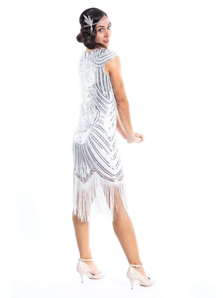 A white flapper dress with silver sequins, beads and white fringes around the hem - back view