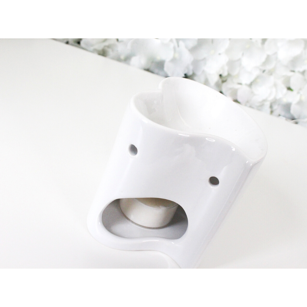 Close up of heart shaped gloss white tealight wax burner