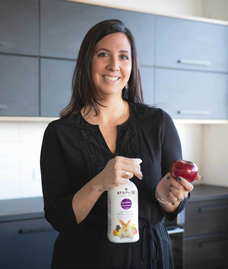 Woman standing while using ATTITUDE Fruit and Vegetable Wash Spray on an apple_en?_team?