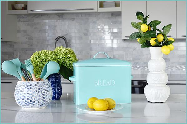 Vintage farmhouse bread bin in mint on counter with utensil holder, lemons, white vase and hydrangea flowers