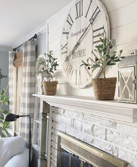 Clock and plants on a white fireplace mantle