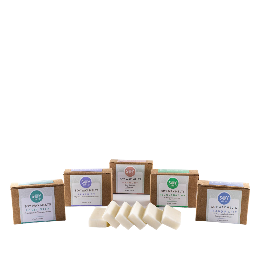 SoyLites Soy Wax Melts. 6 wax melts unwrapped, with five packaged boxes behind them in each scent. From left to right, Positivity, Serenity, Harmony, Rejuvenation, and Tranquilty.