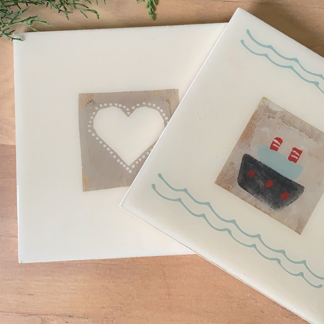 Trivets with recycled tea bags and designs. Heart and sailboat.