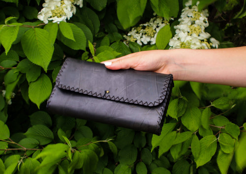 Sheek, black clutch purse hand crafted from recycled car tires in South Africa.
