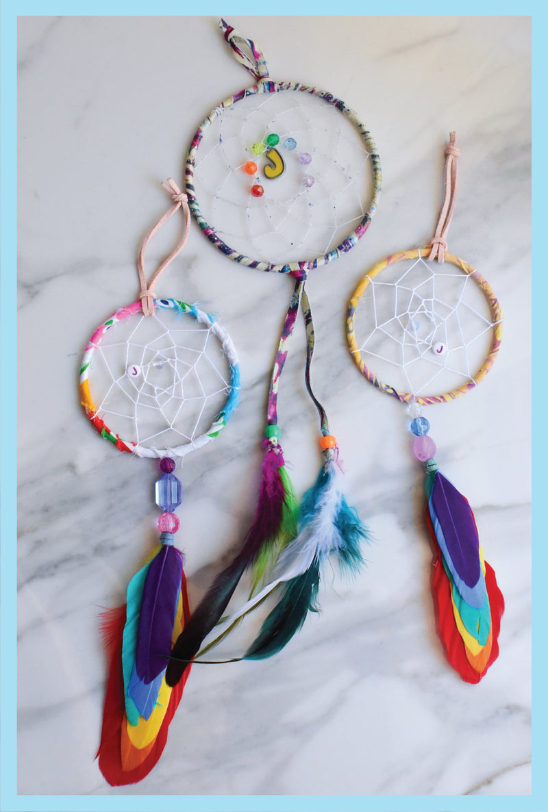 three dream catchers made with colourful ropes, beads and feathers on a marble background