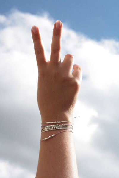 woman's hand making a peace sign to the clouds above, wearing a stack of string and bead wish bracelets