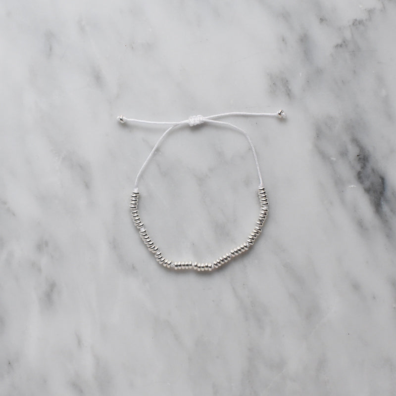 white knotted nylon thread and sterling silver bracelet